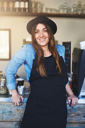 mandil: Individual barista linda mujer vistiendo la camiseta azul, delantal negro y sombrero con expresión alegre que se inclina contra contador de metal y madera en café