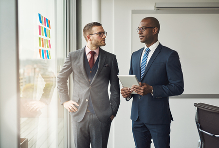 team leadership: Two smart business managers or office co-workers in a discussion standing in front of a window with colorful memos on the glass