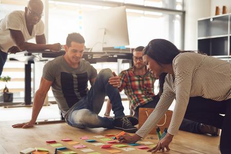 Grupo de cuatro empleados de reuniones en torno a diversas notas adhesivas de colores en el piso de madera dura en la pequeña oficina