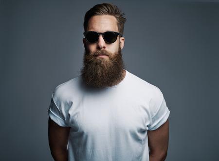 ハンサムな独身ひげを生やした若い白人男性灰色の背景上の真剣な表情と白い半袖シャツとサングラスの肖像画 写真素材
