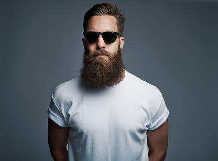 Portrait of handsome single bearded young Caucasian man wearing sunglasses with serious expression and white short sleeve shirt over gray background Фото со стока