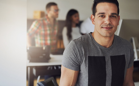 small office: Close up of handsome male worker wearing gray short sleeve shirt in small office with other employees behind him Stock Photo