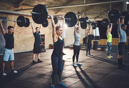 los jóvenes de ajuste de elevación pesas mirando enfocados, que se resuelve en un gimnasio Foto de archivo