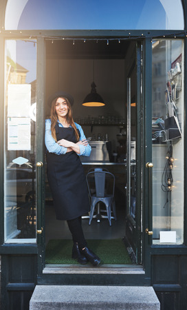 nonchalant: Single cute female barista in apron and hat with folded arms leaning against doorway in cafe Stock Photo