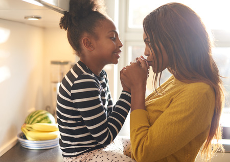 Mother kissing her daughter at home in kitchen, black woman Stock Photo - 59229869