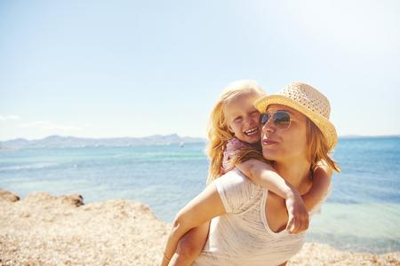 familia animada: Riendo vivaz niña rubia con su madre en la playa montar en ella de una lengüeta en una orilla rocosa, el contexto del océano y de la copia Foto de archivo