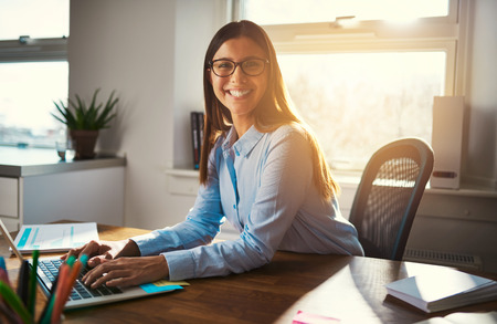 colores calidos: Female entrepreneur at desk smiling at camera, blue warm colors