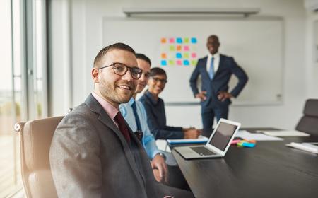 Grupo de cuatro adultos profesionales jóvenes negros, hispanos y caucásicos en una reunión en su oficina cerca de gran tablero parcialmente cubierto con notas adhesivas de colores