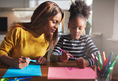 black art: Mom and child drawing in kitchen, black mother and daughter Stock Photo