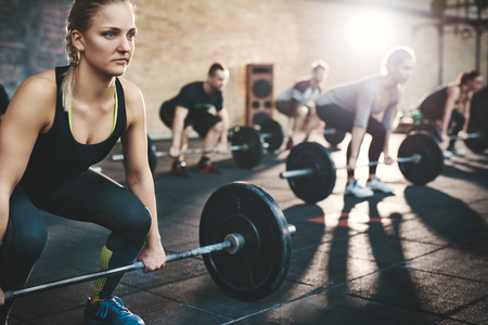 Fit junge Frau Aufhebung Hanteln konzentriert suchen, mit anderen Menschen in einem Fitness-Studio trainieren