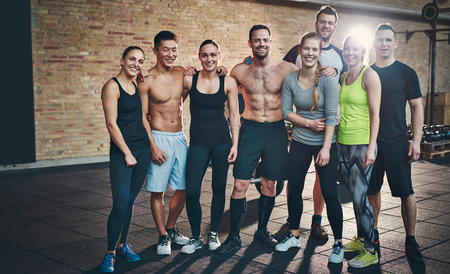 Gruppe von acht athletische junge weibliche und männliche Erwachsene, die zusammen als gute Freunde in der Turnhalle nach einem schwierigen Trainings-Sitzung stehen