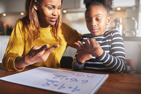 learning by doing: Excited child learning to calculate at home, black mother and daughter doing homework