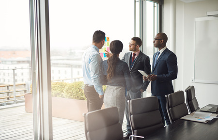 management team: Diverse multiracial management team standing grouped in front of a large bright window in the conference room discussing colorful memos on the glass Stock Photo