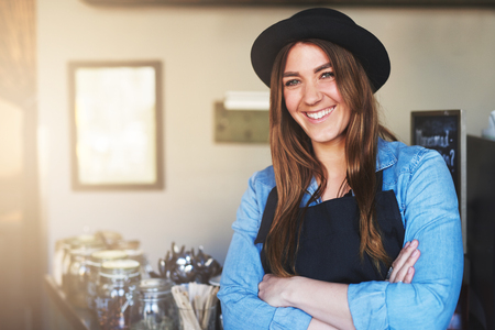 self assured: Young brunette wearing black hat and apron standing with arms folded and smiling