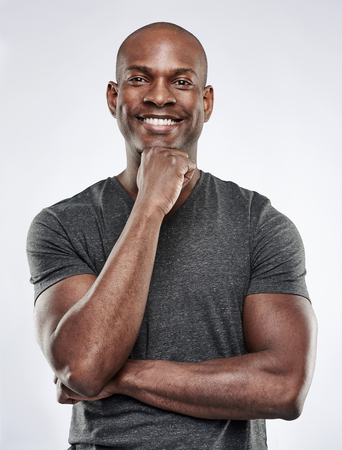 Single knappe fit Zwarte man met geschoren hoofd, de armen over elkaar en met de hand op de kin, terwijl lachend