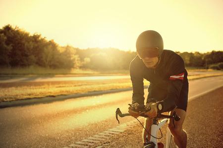 iluminado a contraluz: Solo hombre en el casco de seguridad y gafas de sombra que montan en bicicleta solos por la carretera desierta, con copia espacio sobre el camino Foto de archivo