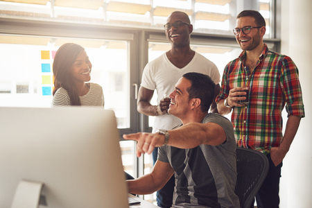 Handsome male adult pointing at something on his computer for a group of laughing male and female casually dressed friends holding drinks