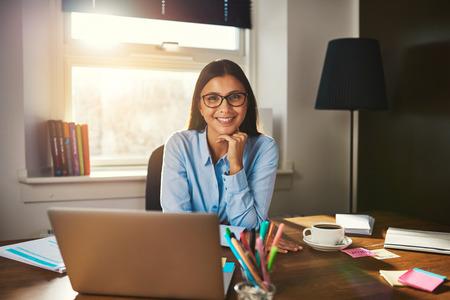 Vrouwelijke ondernemer zit aan bureau glimlachend op camera