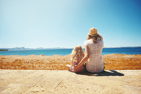 Young mother and her small blond daughter sitting on the seashore looking out over the ocean with their backs to the camera and copy space Stock Photo