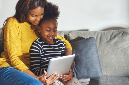 Black mom and child with tablet having a good time smiling and learning Stock Photo