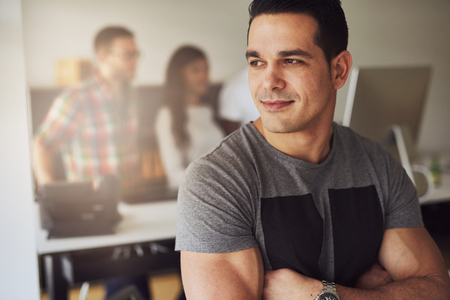 preoccupied: Close up of calm handsome male worker with folded muscular arms wearing gray short sleeve shirt in small office with other employees behind him
