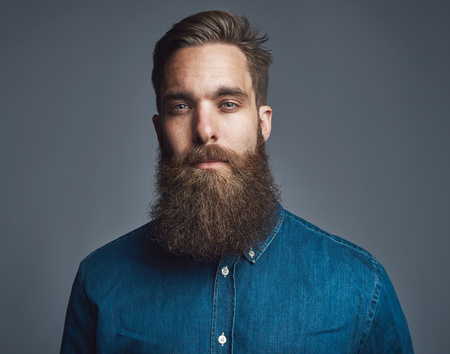 sombre: Head and shoulders straight on portrait of handsome bearded man in blue denim shirt and serious expression over gray background