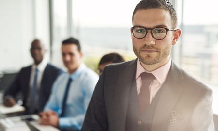 Serious young businessman in a meeting with multiracial colleagues standing looking intently at the camera with sun flare over his shoulder