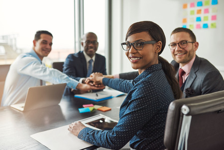 Successful African American team leader turning to smile at the camera as her multiracial team of executives links hands across the table Stockfoto