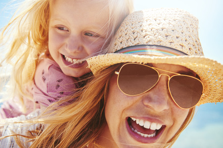 child laughing: Laughing young mother in a trendy hat and sunglasses giving her little daughter a piggy back outdoors in the summer sunshine with the breeze blowing their long blond hair, close up head shot