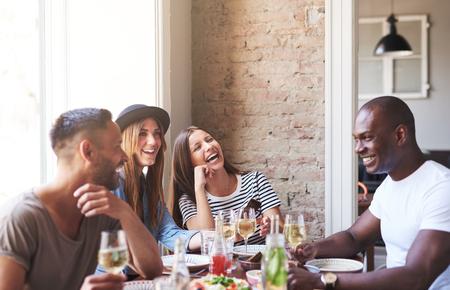 Diverse piccolo gruppo di quattro amici felici con il vino e la cena insieme al ristorante con muro di mattoni e luminoso grande finestra in background