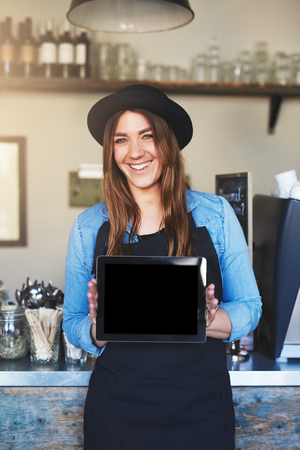 outwards: Female entrepreneur wearing black hat and apron smiles at camera while holding computer tablet outwards between both hands