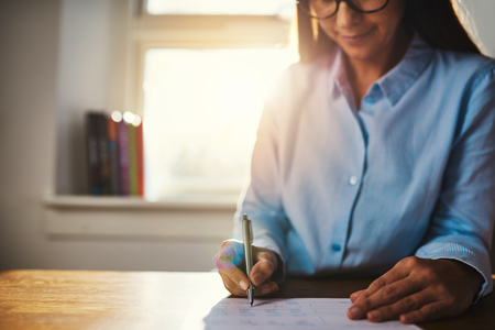 low blouse: Selective focus on hands of single woman in blue blouse working at desk on paperwork in home office with sunlight over her shoulder through window Stock Photo