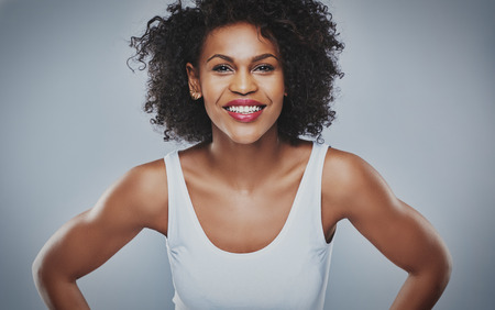centered: Front centered view on smiling female with enthusiastic expression leaning forward over gray background