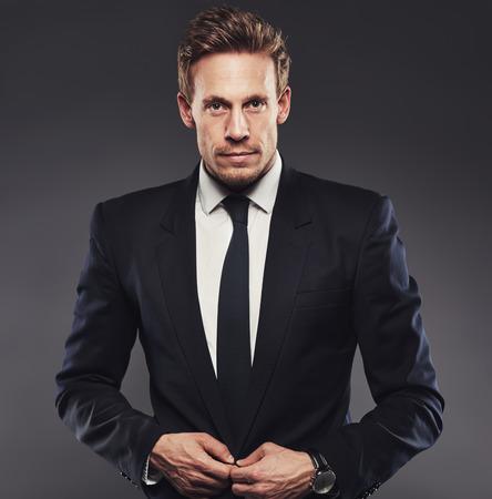 chaqueta: apuesto joven en un traje negro botones de su chaqueta, de pie sobre un fondo gris Foto de archivo