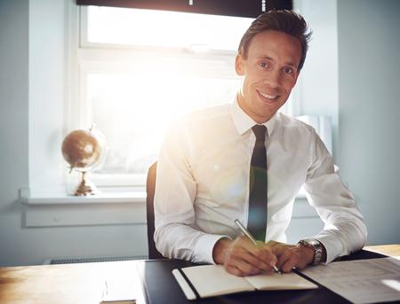 흰 셔츠와 넥타이를 착용하고 카메라를 웃고있는 동안 메모를 쓰는 비지니스 맨 임원 스톡 콘텐츠
