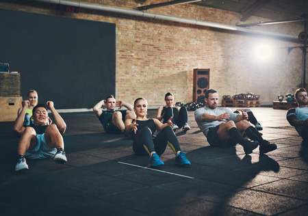 Group of athletic adult men and women performing sit up exercises to strengthen their core abdominal muscles at fitness training Фото со стока