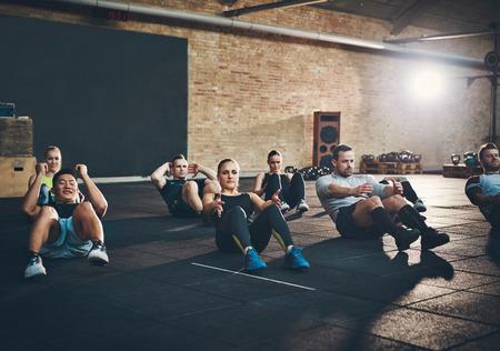 Grupo de hombres y mujeres adultos atléticos realizan sentarse ejercicios para fortalecer sus músculos abdominales centrales en la formación de la aptitud Foto de archivo