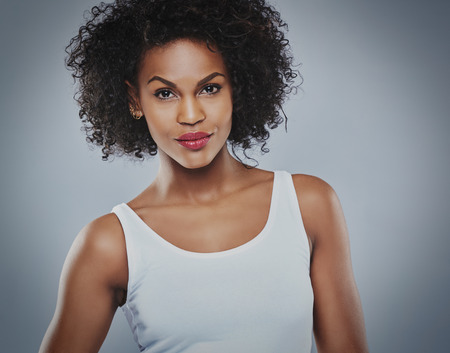 near side: Calm single serious Black woman in white sleeveless undershirt posed confidently over gray background with copy space Stock Photo