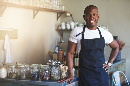 Handsome black entrepreneur stands by cafe counter lined with jars of tea while wearing dark colored apron
