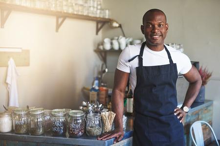 Knappe zwarte ondernemer staat bij cafe teller vol met potjes van thee, terwijl het dragen van donker gekleurde schort