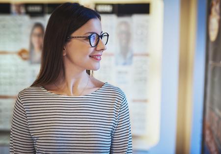 eye wear: Cute young woman looking sideways in new eyeglasses in front of display at eye wear shop