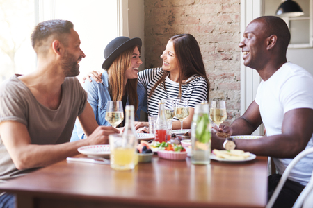 camaraderie: Laughing young men watching their girlfriends embrace each other at restaurant with large bright window and brick wall
