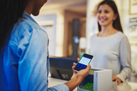 salesperson: Customer paying with phone and pin pad in front of smiling cashier salesperson at store