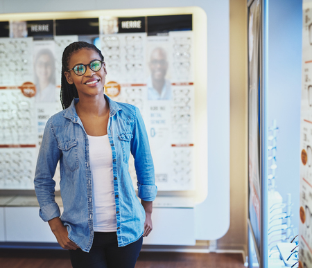 eye wear: Single smiling pretty Black woman in eyeglasses with both hands in pockets while standing in front of display at eye wear shop