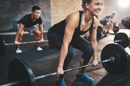 Wesoła muskularna młoda kobieta z kucykiem i czarnych rajstop wykonujących martwego podnoszenia sztangi ćwiczenia z innymi studentami