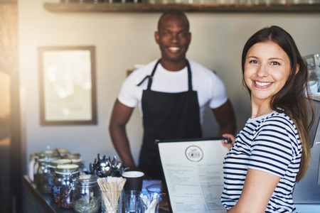hospitality industry: Beautiful young woman in striped shirt with cheerful expression holding menu near young African coffee house owner in apron taking her order