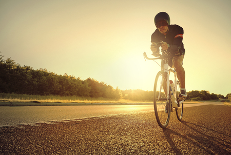 Le bicyclette masculin simple est rétro-éclairé par la lumière du soleil lumineuse et jaune tout en parcourant son vélo sur le vélo de route au lever du soleil