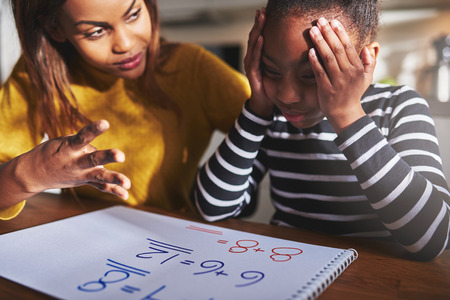 sums: Mother learning child to calculate, child looking frustrated. Black woman and child