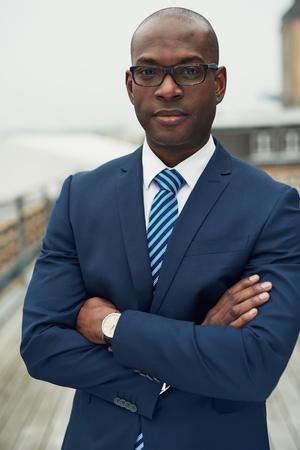 Vertrouwen in stijlvolle Afro-Amerikaanse zakenman die zich met gevouwen armen op een balkon aandachtig kijken naar de camera, close-up bovenlichaam