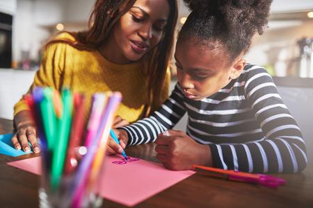Maman et enfant dessin dans la cuisine, la mère et la fille noire